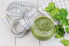 A tasty and healthy spinach smoothie and a centimeter to measure the results of a diet. Royalty Free Stock Images