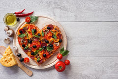 Tasty heart shaped pizza decorated with vegetables and herbs on white wooden background. Stock Photography