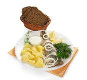 Tasty herring, potatoes with sauce and a bread. With basket on a orange napkin, isolated on white Royalty Free Stock Images