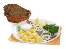 Tasty herring, potatoes with sauce and bread. Tasty herring, potatoes with sauce and a bread with basket on a orange napkin, isolated on white Royalty Free Stock Photo