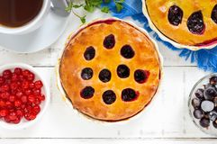 Tasty homemade berry pies in a round ceramic form, a cup of tea Royalty Free Stock Image