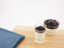 The tasty homemade blueberry panna cotta (Italian pudding dessert) in the small glass and blue cotton fabric Stock Photography