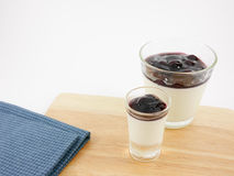 The tasty homemade blueberry panna cotta (Italian pudding dessert) in the small glass and blue cotton fabric Royalty Free Stock Image