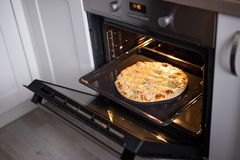 Tasty homemade cheese pizza in oven stock photos