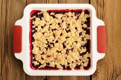 Tasty homemade cherry oat crumble in square white baking dish on. Wooden table topview horizontal stock photography