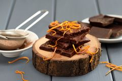 Tasty homemade chocolate bars decorated with orange peels on woo Royalty Free Stock Photography