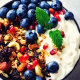 Tasty homemade granola, yogurt, fresh organic berries, pomegranate, mint on grey concrete background with copy space. Top view. Square crop Stock Photos