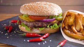 Tasty homemade hamburger with potatos served on stone plate stock video footage