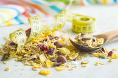 Tasty homemade muesli with nuts in bowl with measuring tape. Royalty Free Stock Photos