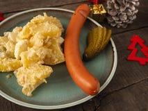 Tasty Christmas food with potato salad. Tasty homemade potato salad with organic sausage and gherkin, traditional Christmas meal Stock Image