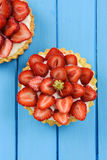 Tasty homemade tarts with fresh sweet strawberries and mascarpone cheese on blue table. Vertical with copyspace stock photography