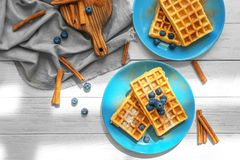 Tasty homemade waffles with sugar powder, cinnamon sticks and blueberries Royalty Free Stock Photos