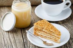 Tasty honey cake with jar of honey. Stock Image