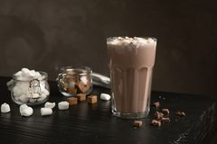 Tasty hot chocolate with milk and marshmallows. In glass on table stock photography
