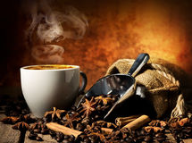 Tasty hot coffee. With grains and spices on table stock photo