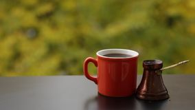 Tasty hot coffee in red coffee cup brewed in traditional turkish pot, cafe table outdoors. Autumn background stock video footage