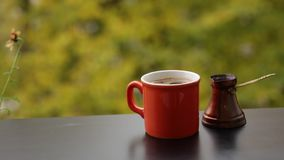 Tasty hot dark coffee brewed in traditional turkish coffee pot, cafe table on veranda stock video