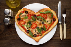 Tasty hot pizza in heart shape with chicken and mushrooms and cutlery on wooden table. Fresh italian dish for Valentines day. Top view Royalty Free Stock Photos