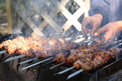 Tasty hot shish kebab. Appetizing shish kebab on the grill with metal skewers Royalty Free Stock Images