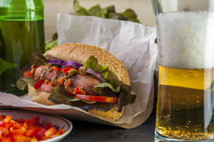 Tasty hotdog, beer glass and bottle Stock Image