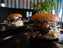 Tasty huge burgers in a restaurant - at a table royalty free stock photo