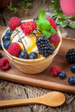 Tasty ice cream dessert with fruit in a waffle bowl. Selective focus Stock Image