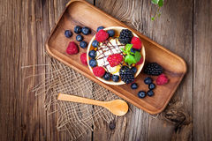 Tasty ice cream dessert with fruit in a waffle bowl. Selective focus. Top view Stock Images