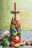 Tasty infused water in bottle with drink straw and ingredients, front view. Water Flavored with colorful fruits, berries and herbs. Summer drinks. Healthy and royalty free stock photos