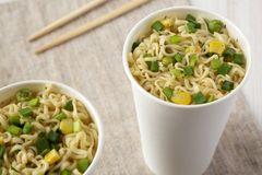 Tasty instant noodles with beef flavoring in paper cups, low angle view. Closeup. Tasty instant noodles with beef flavoring in paper cups, low angle view stock photography
