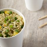 Tasty instant ramen noodles with beef flavoring in paper cups, low angle view. Closeup. Tasty instant ramen noodles with beef flavoring in paper cups, low angle stock image