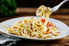 Tasty Italian carbonara spaghetti twirled on a fork. Ready for eating a mouthful suspended above a plateful of noodles Royalty Free Stock Images