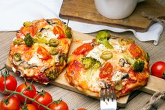 Tasty Italian homemade mini pizzas with broccoli, feta and olives. Served on wooden cutting board Royalty Free Stock Photo