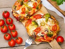 Tasty Italian homemade mini pizzas with broccoli, feta and olives Royalty Free Stock Photo