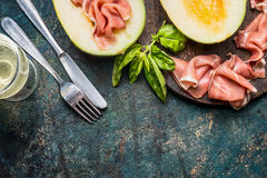 Tasty italian lunch with ham, melon , cutlery and wine on dark rustic vintage background, top view Stock Photo