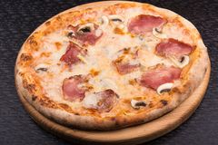Tasty italian pizza with bacon and mushrooms Royalty Free Stock Images