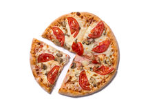Tasty Italian pizza with ham and tomatoes with a slice removed. Isolated on white background stock image