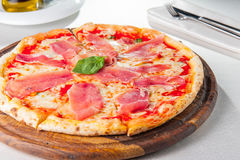 Tasty  Italian pizza topped with thinly sliced prosciutto ham on the served restaurant table. Selective focus Royalty Free Stock Photography
