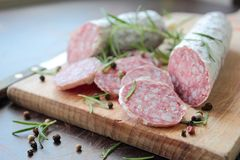 Tasty italian salami sausage. Salami sausage sliced on wooden board with herbs royalty free stock image