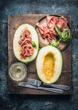 Tasty jamon serrano prosciutto ham and melon with glass of white vine and cutlery Stock Photo