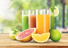 Tasty fruits and juice on wooden table. Tasty juice fruits color nobody vibrant horizontal Royalty Free Stock Photography