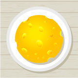 Tasty juicy round piece of cheese on a plate Royalty Free Stock Photography