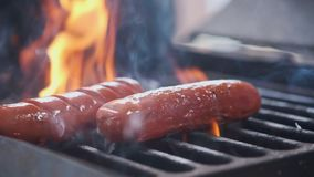 Tasty juicy sausages grilling over a fire. Cook man preparing sausages on the grill. Throws on the grill and flips over
