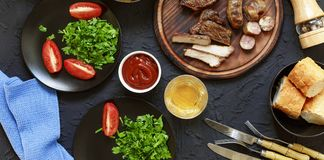 Tasty and juicy steaks, various fresh vegetables,. Greens, wine and beer on a black stone background. Concept: dinner in a restaurant Stock Photos