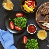Tasty and juicy steaks, various fresh vegetables,top veiw. Tasty and juicy steaks, various fresh vegetables, greens, wine and beer on a black stone background Royalty Free Stock Photo