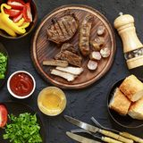 Tasty and juicy steaks, various fresh vegetables,top. Tasty and juicy steaks, various fresh vegetables, greens, wine and beer on a black stone background Royalty Free Stock Photo