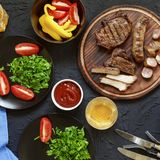 Tasty and juicy steaks, various fresh vegetables, top veiw. Tasty and juicy steaks, various fresh vegetables, greens, wine and beer on a black stone background Stock Photos