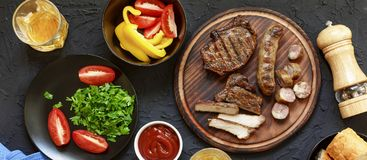 Tasty and juicy steaks, various fresh vegetables,top veiw. Tasty and juicy steaks, various fresh vegetables, greens, wine and beer on a black stone background Stock Photography