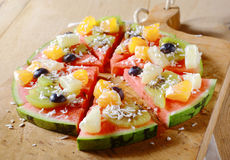 Tasty juicy tropical fruit watermelon pizza. A tasty juicy fresh tropical fruit watermelon pizza topped with kiwifruit, blueberries, orange, pineapple, and Royalty Free Stock Image