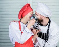 Tasty kiss. Family cooking in kitchen. secret ingredient by recipe. cook uniform. man and woman chef in restaurant. Tasty kiss. Family cooking in kitchen. secret royalty free stock photo