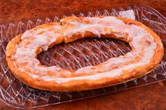 Tasty Kringle pastry in oval shape. An oval white iced Danish Kringle on a clear tray over a dark burl surface royalty free stock photos